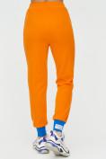Оптом Спортивные брюки женские оранжевого цвета 1307O в Екатеринбурге, фото 11